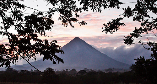 The Arenal volcano at dawn, surrounded by early morning mist.