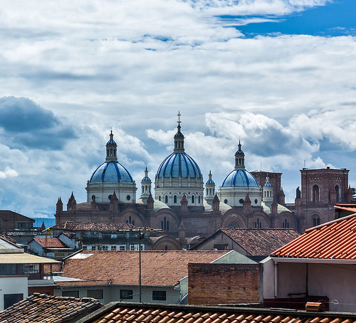 "In Cuenca, you'll see gorgeous views of the city's iconic red tile roofs and the blue domes of the famous ""new cathedral."""