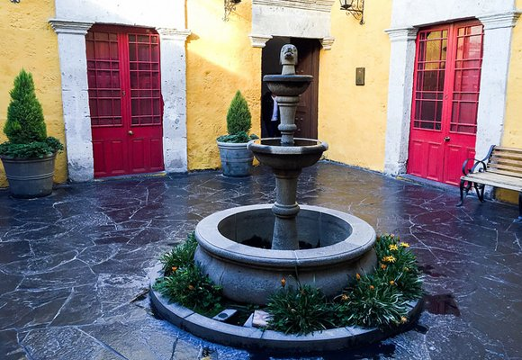 The colonial style home usually features an interior courtyard, often with a fountain and potted plants like this one in Arequipa, Peru.